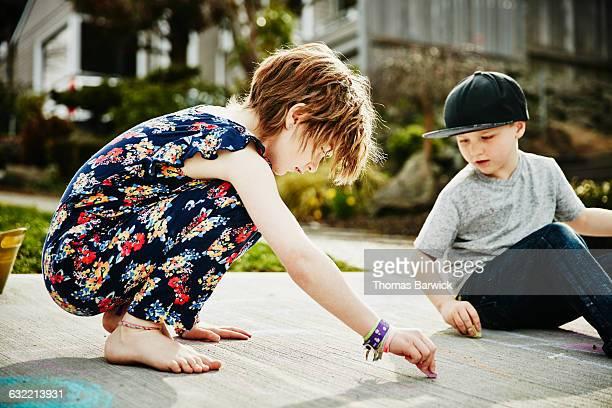 Siblings drawing with chalk on sidewalk