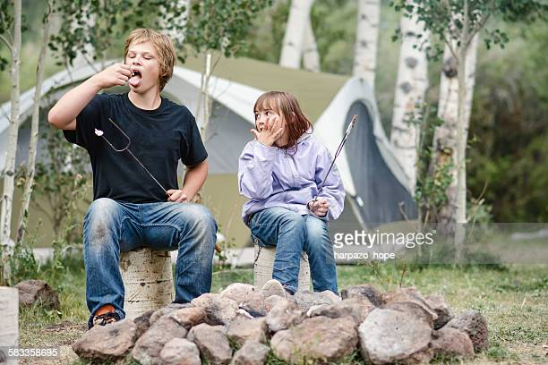 Siblings eating marshmallows