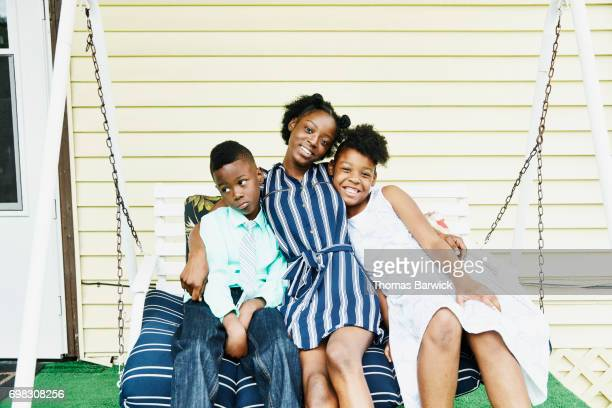 Siblings embracing on swing on front porch of home