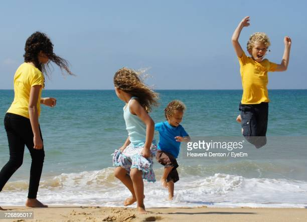 Siblings Enjoying On Shore At Beach Against Sky