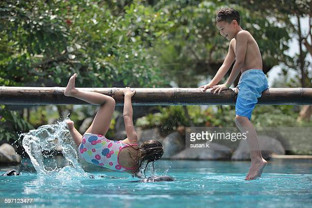 Siblings happily playing plank game at the pool.