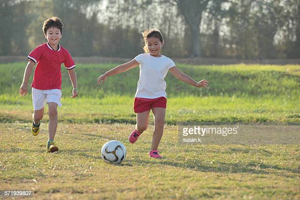 Siblings happily playing soccer