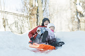 Siblings are having downhill fun on winter plastic snow slider outdoors