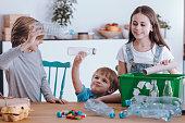 Siblings having fun while segregating waste at home