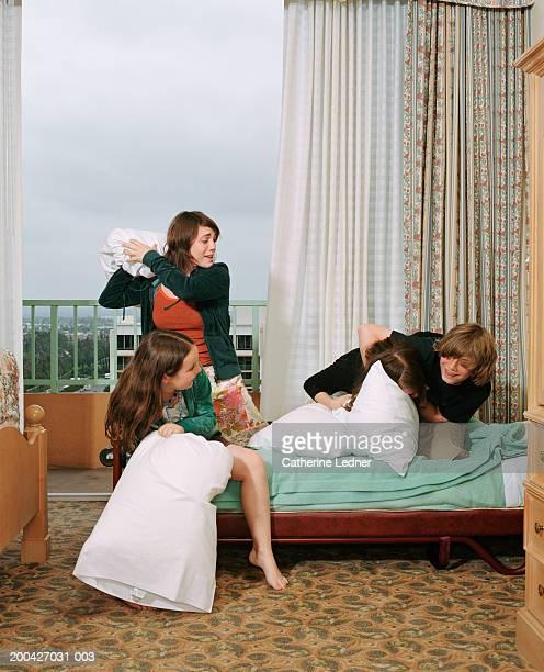 Siblings having pillow fight in room