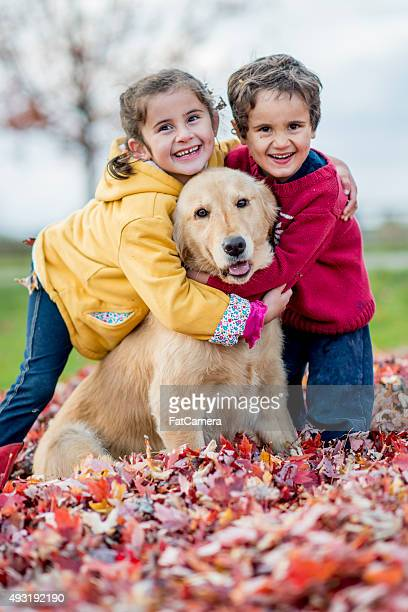 Siblings Hugging Their Dog on a Fall Day