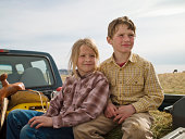 Brother and sister in the back of pick-up trunk in Big Timber, Montana