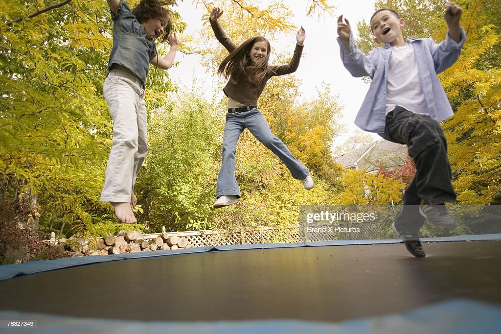 Siblings jumping on trampoline : Stock Photo