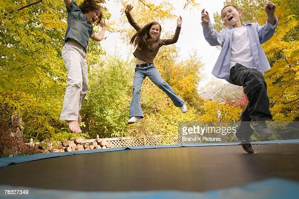 Siblings jumping on trampoline