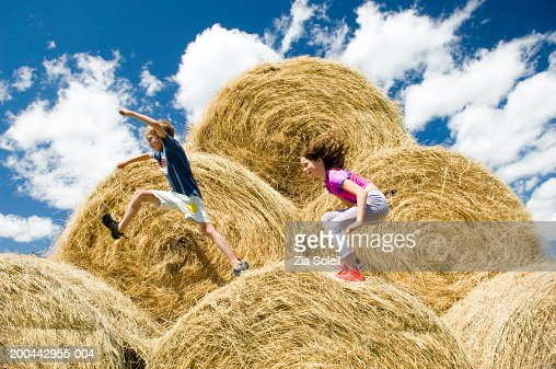 Siblings (7-11) leaping across bales of hay, side view : Stock Photo