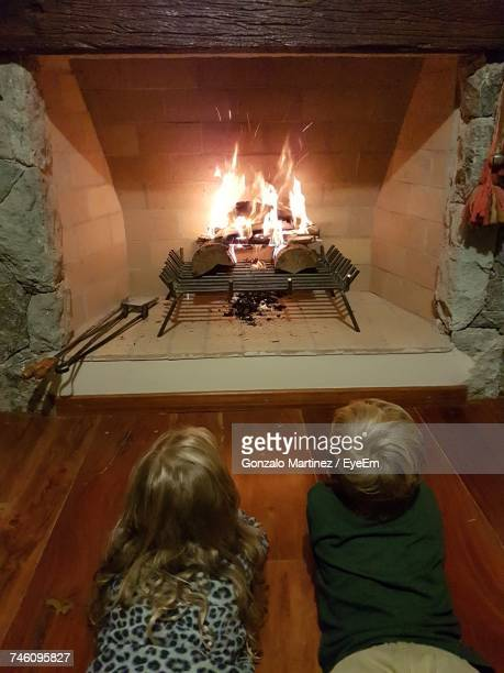 Siblings Lying On Hardwood Floor By Fireplace At Home