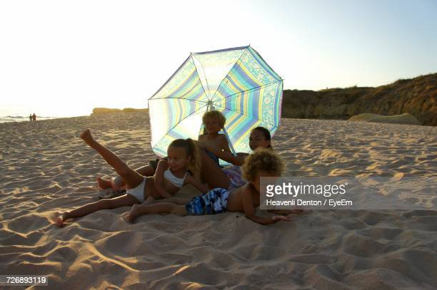 Siblings Lying On Sand At Beach Against Sky During Sunset
