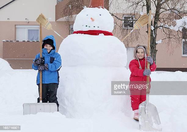 Siblings making giant snowman at the backyard.
