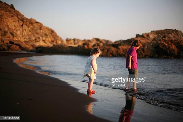 Siblings paddling on beach in evening