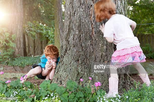 Frères et sœurs jouent à cache-cache dans le jardin