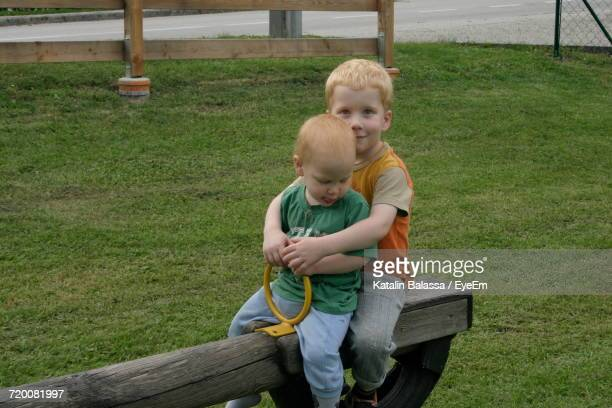Siblings Playing On Seesaw At Playground