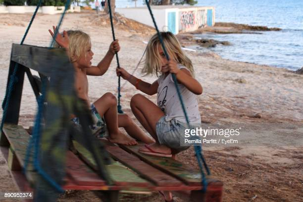 Siblings Playing On Swing At Beach