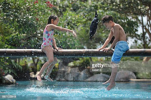 Siblings playing pillow fight game at the pool