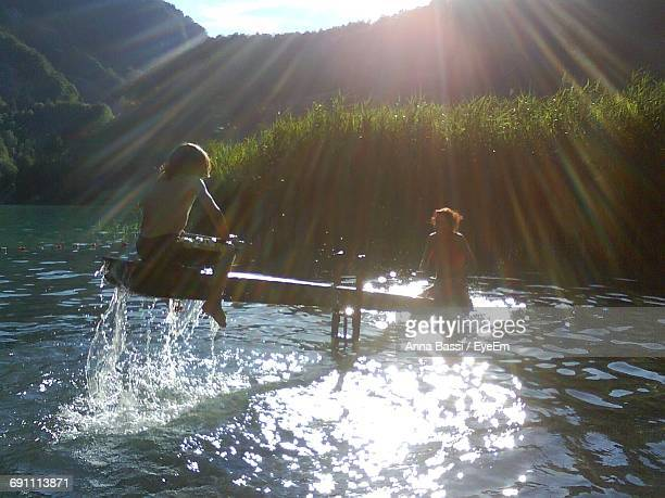 Siblings Playing Seesaw In Lake Against Mountains On Sunny Day