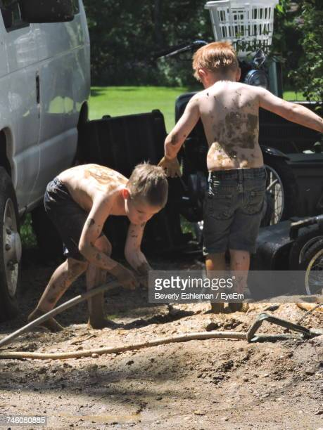 Siblings Playing With Mud In Yard