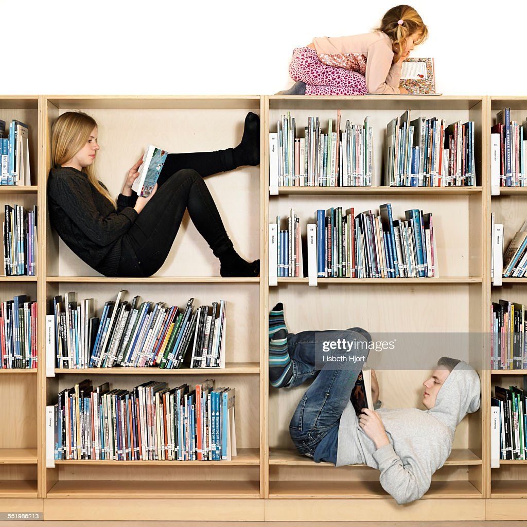 Siblings reading on book shelf : Stock Photo