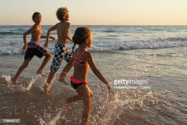 Siblings Running On Shore At Beach Against Sky During Sunset