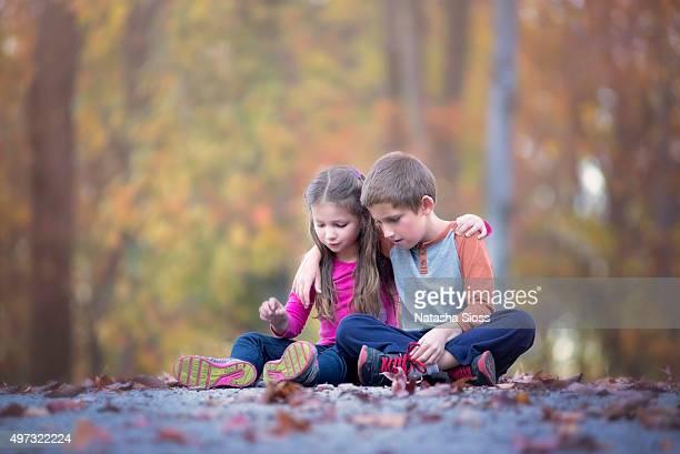 Siblings sitting in the driveway