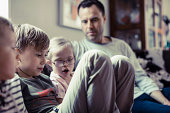 Siblings sitting with father in house