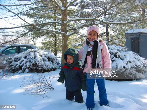 Siblings Standing By Tree On Snow Covered Field