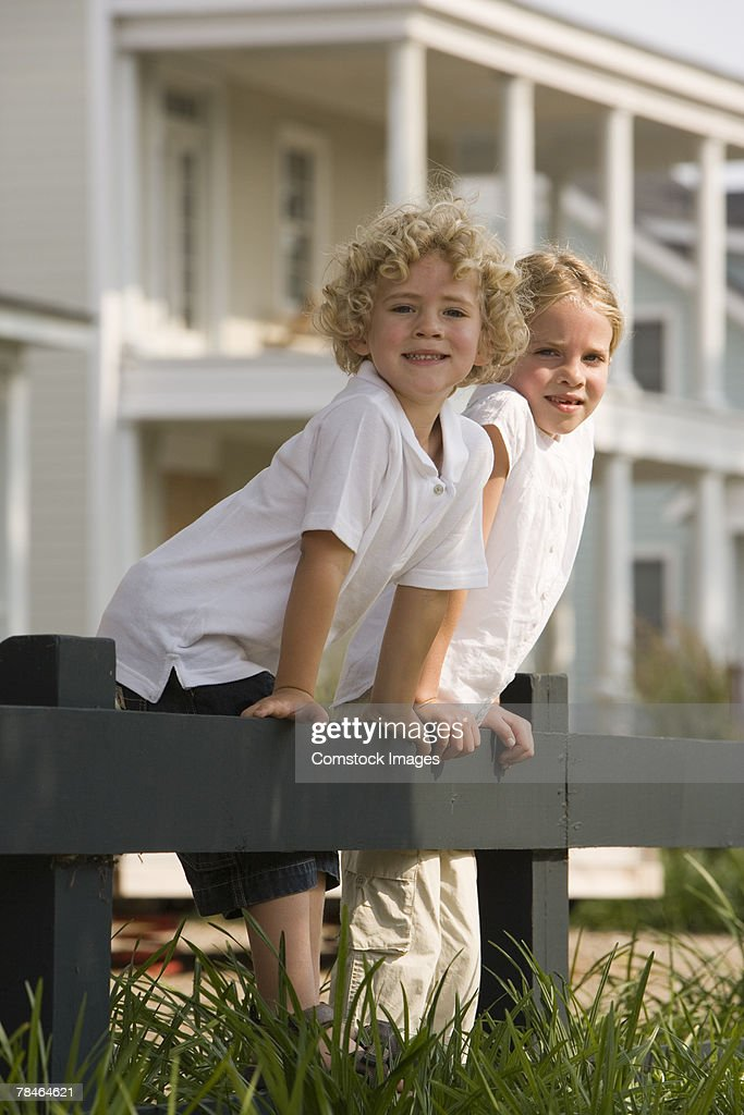 Siblings standing on fence : Stock Photo