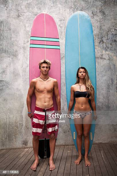 Siblings staring at camera w/vertical surfboard