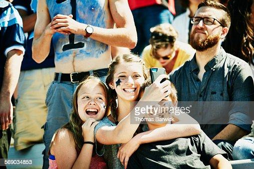 Siblings taking selfie during football game
