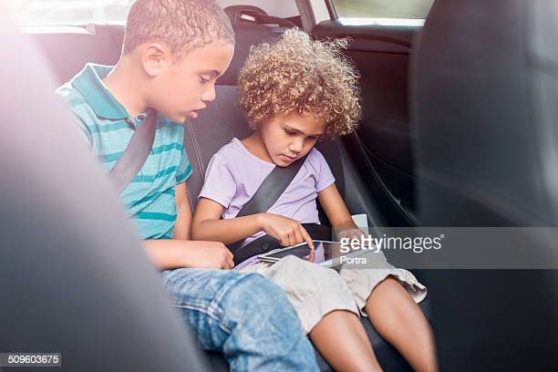 Siblings using digital tablet in car