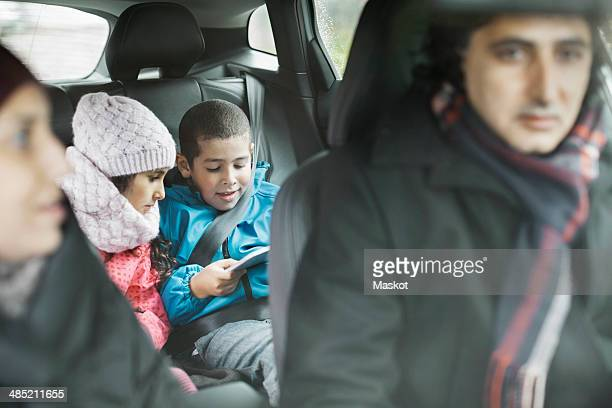 Siblings using digital tablet while on road trip with parents