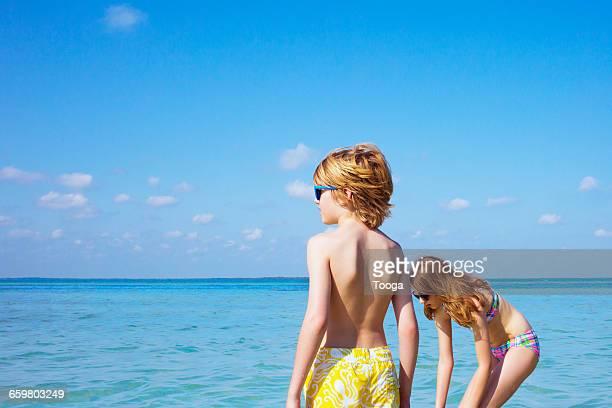 Siblings wading in blue ocean