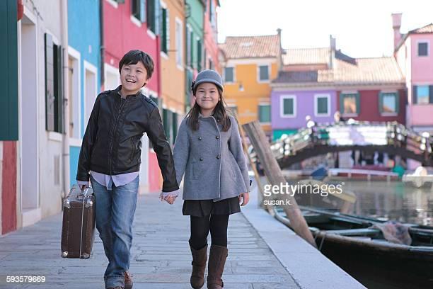 Siblings walking hand in hand at Burano