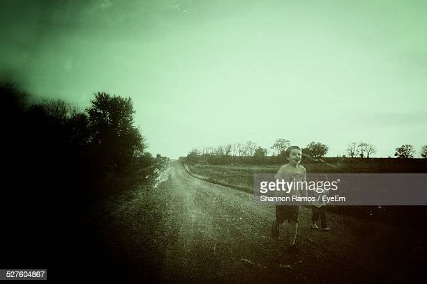 Siblings Walking On Country Road
