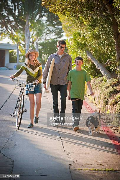siblings walking with surfboard, bicycle and dog