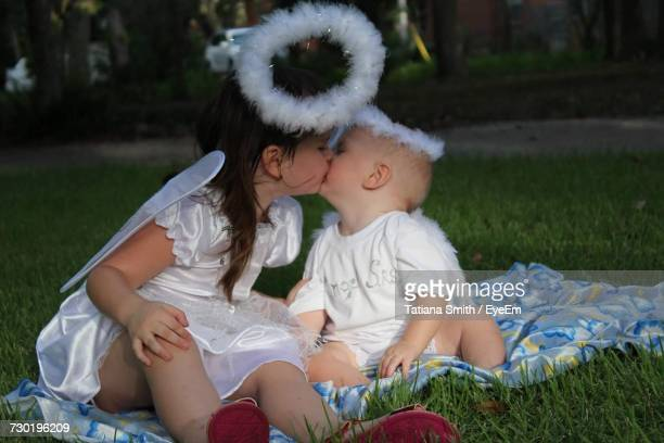 Siblings Wearing Fairy Costume Kissing While Sitting On Grassy Field