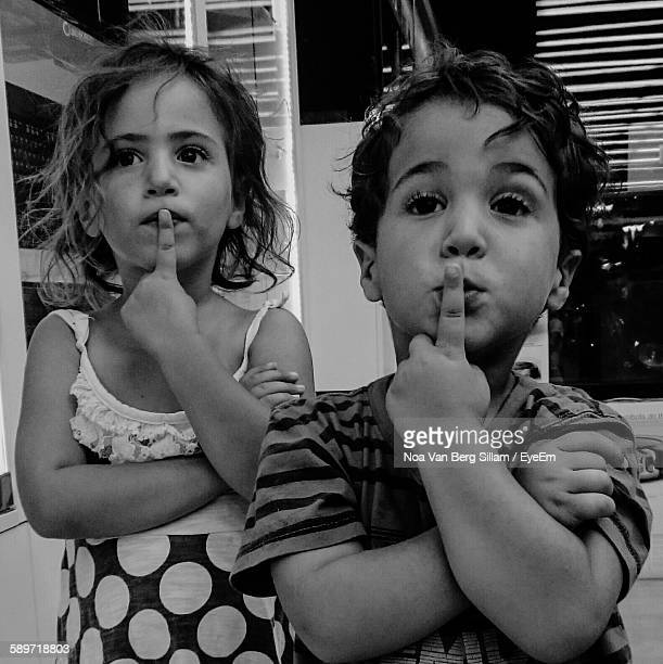 Siblings With Finger On Their Lips Standing At Home
