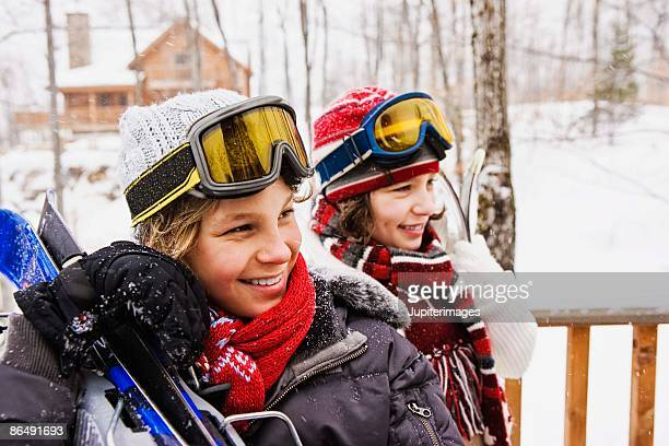 Siblings with ski equipment outdoors