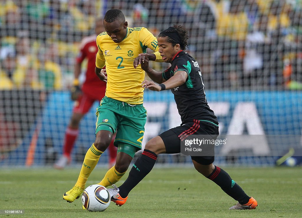 Siboniso Gaxa of South Africa is challenged by Giovani Dos Santos of Mexico during the 2010 FIFA World Cup South Africa Group A match between South...