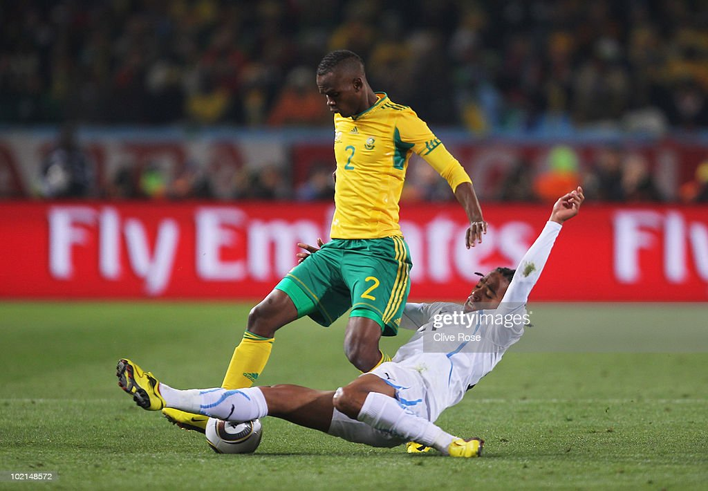 Siboniso Gaxa of South Africa is tackled by Alvaro Pereira of Uruguay during the 2010 FIFA World Cup South Africa Group A match between South Africa...