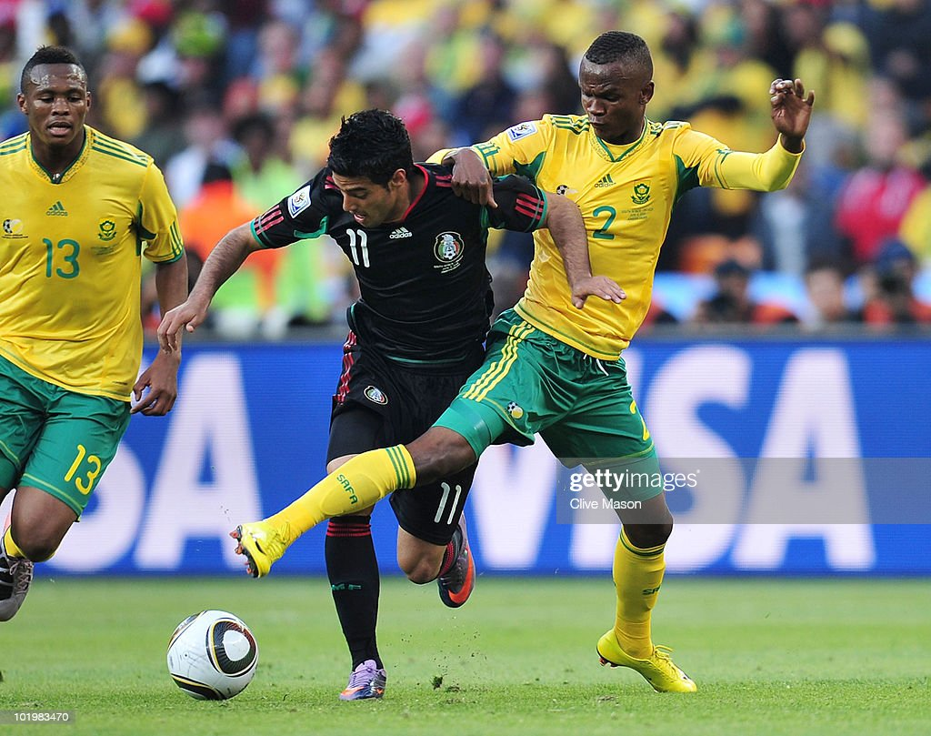 Siboniso Gaxa of South Africa tackles Carlos Vela of Mexico during the 2010 FIFA World Cup South Africa Group A match between South Africa and Mexico...