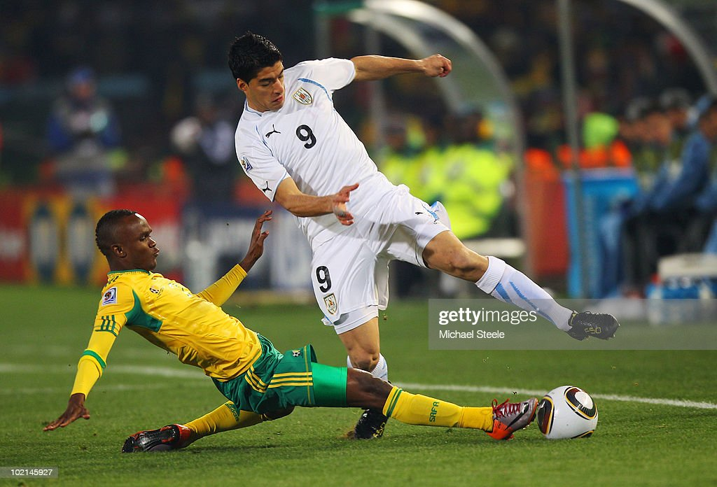 Siboniso Gaxa of South Africa tackles Luis Suarez of Uruguay during the 2010 FIFA World Cup South Africa Group A match between South Africa and...