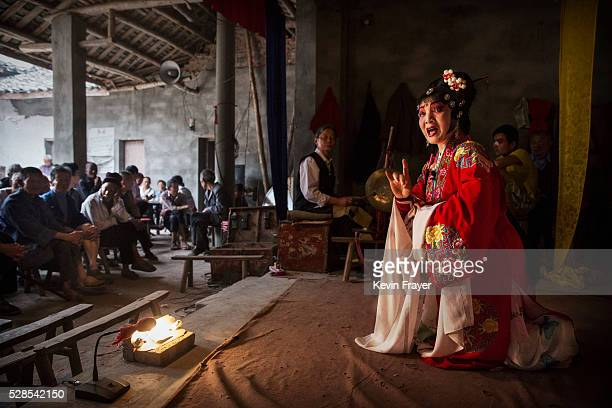 Sichuan Opera actor Lin Lijuan left 69 years of the Jinyuan Opera Company performs for villagers at the Dongyue Temple on May 3 2016 in Cangshan...