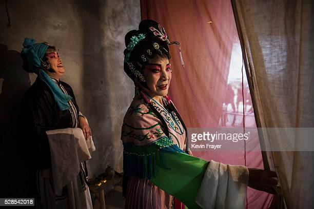 Sichuan Opera performers Lin Lijuan 69 years and Li Qunying 54 years of the Jinyuan Opera Company wait to enter the stage during the group's...