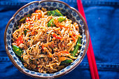 Sichuan spicy pork noodles with bean sprouts, sugar snap peas and oak choi