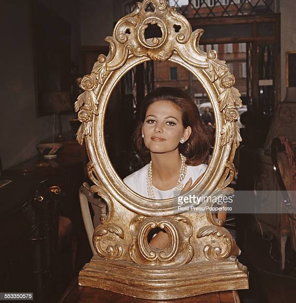 Sicilian actress Claudia Cardinale poses in the centre of a large gilt mirror frame in an antiques shop in Italy in 1965