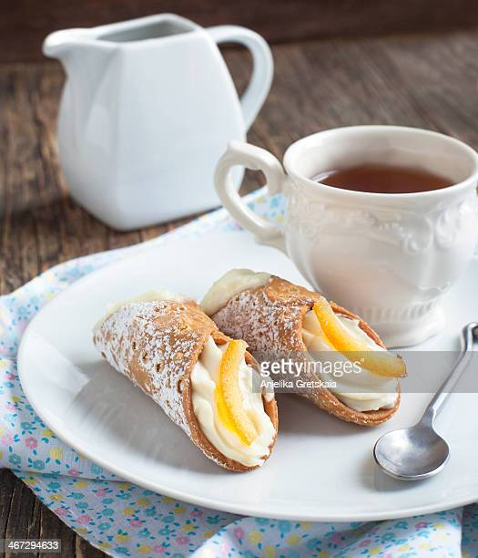 Sicilian cannoli with ricotta cream and cup of tea